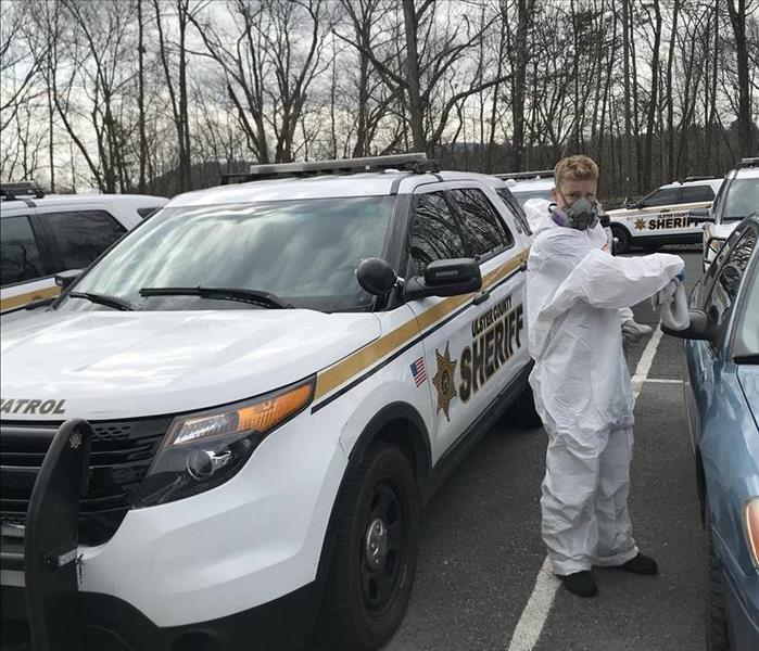 A police officer vehicle parked in a parking lot, with a man in a hazmat suit.
