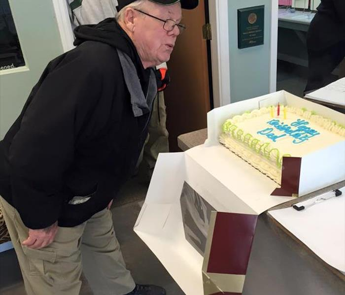 male employee blowing out candles on a birthday cake